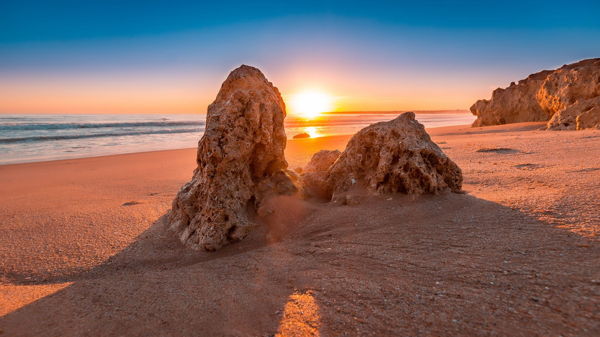 Algarve winter sunset with sun setting between two rocks on the beach