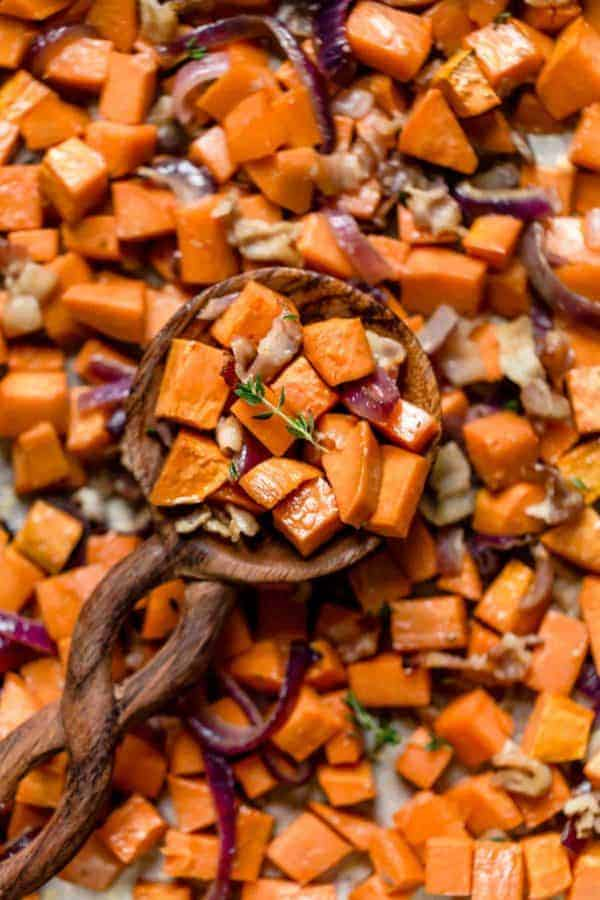 A spoonful of Roasted Sweet Potatoes with Maple and Bacon resting on a sheet pan full