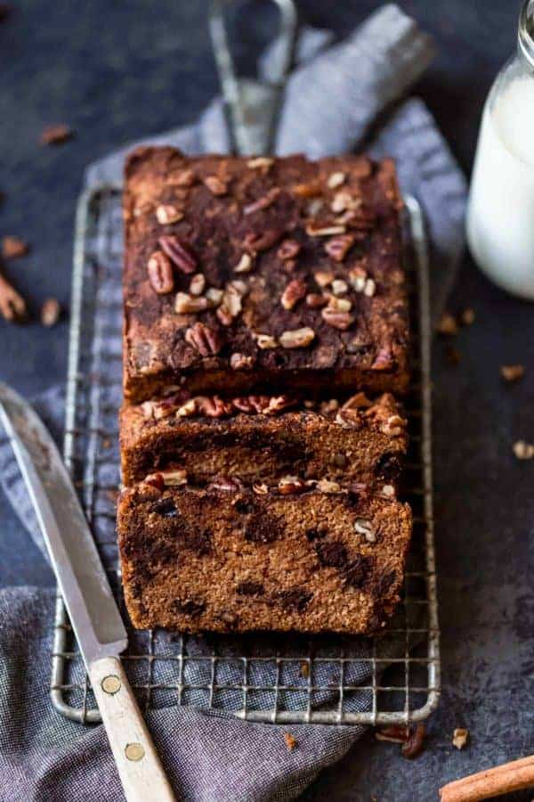 A loaf of gluten-free pumpkin bread with chocolate chips topped with pecans on a wire cooling rack being cut into thick slices.