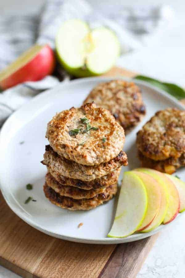 Turkey Apple Sausage Patties stacked on a white plate with a side of apple slices
