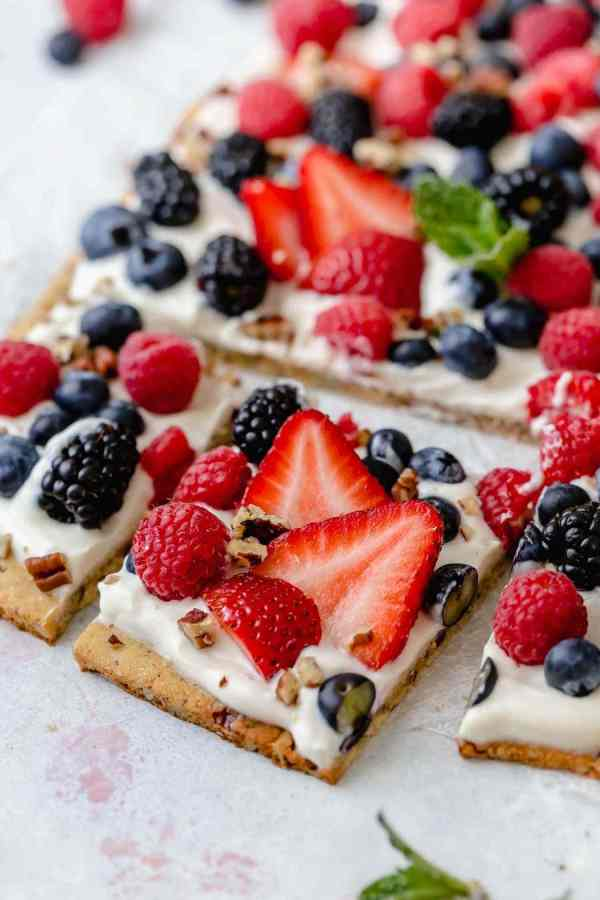 Photo of Gluten-free Berry Fruit Pizza garnished with a sprig of mint in the center. Pizza is topped with a Greek yogurt spread and an assortment of berries. This photo is showing the first row of pizza cut into squares.