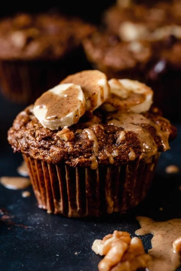 A grain-free sweet potato banana nut muffin topped with banana slices and almond butter.