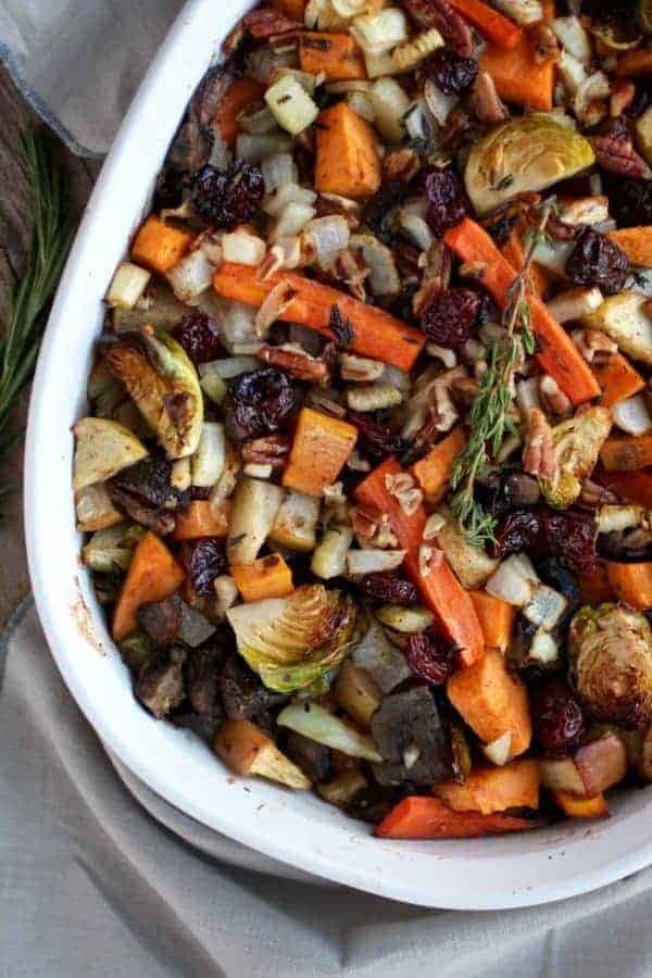 White oval baking dish filled with roasted carrots, Brussels sprouts, carrots, onions, mushrooms, apples, sweet potatoes, celery – Sweet Potato Unstuffing is part of the 12 Healthy Thanksgiving Side Dish Recipes.