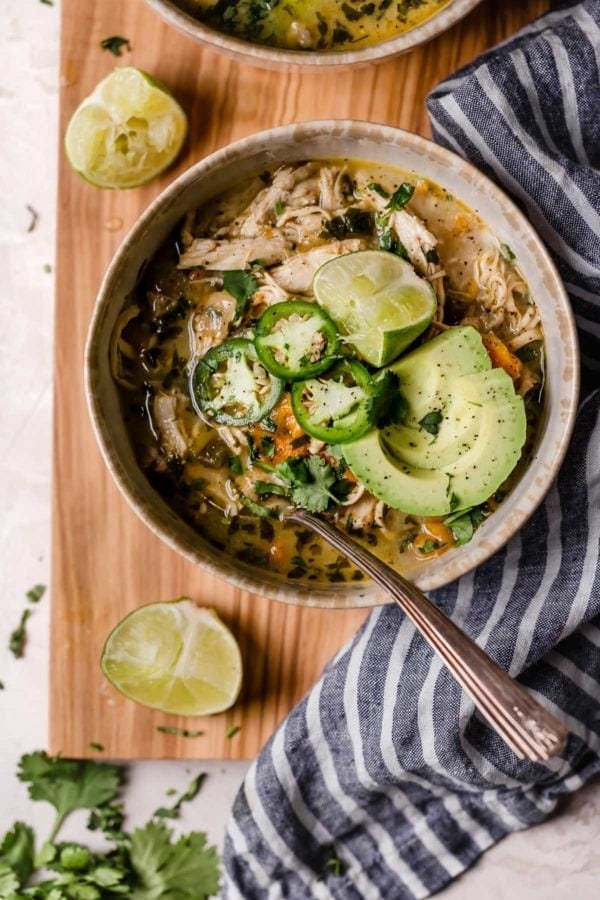 Bowl of white chicken chili with spoon garnished with jalapeños, avocado and limes on wooden cutting board. This recipe ranked #1 of the Most Popular Recipes of 2019.