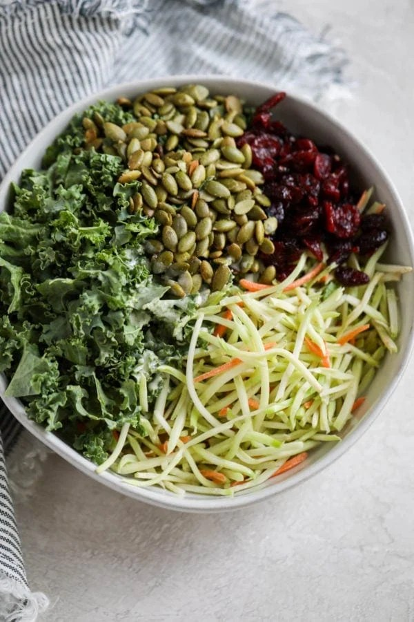 A white serving bowl filled with kale, pumpkin seeds, dried cranberries, and broccoli shreds.