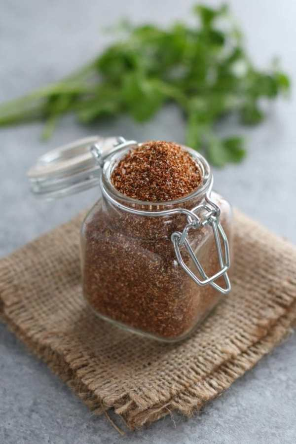Small glass jar filled with taco seasoning resting a square of burlap