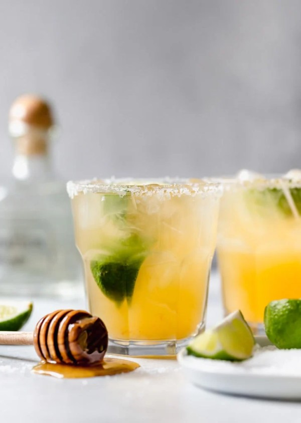 Two margaritas in salted tumblers with a honey-dipped wand laying flat and lime garnishes and a tequila bottle in the background