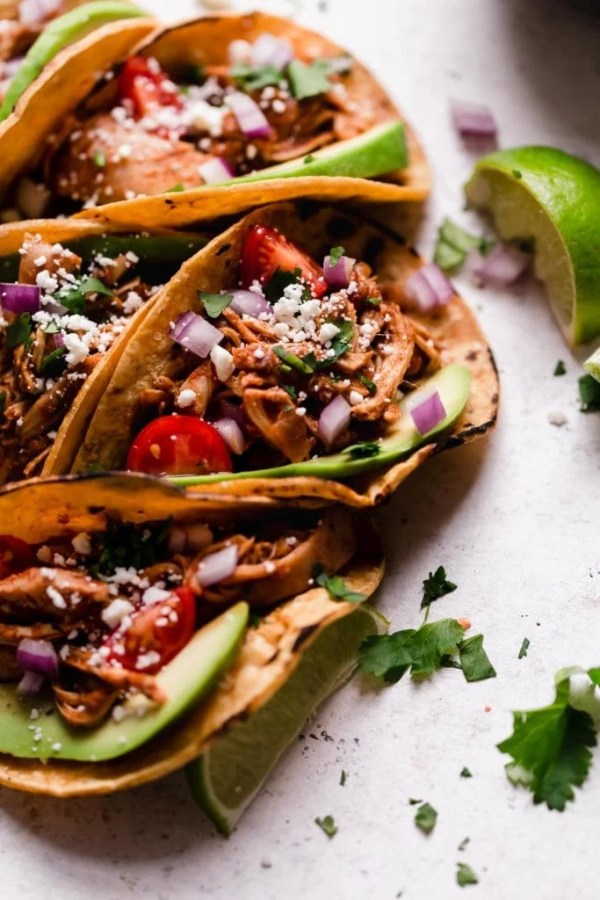 Folded tacos in corn tortillas with avocado, tomatoes, onions and chicken with limes and cilantro surrounding them.