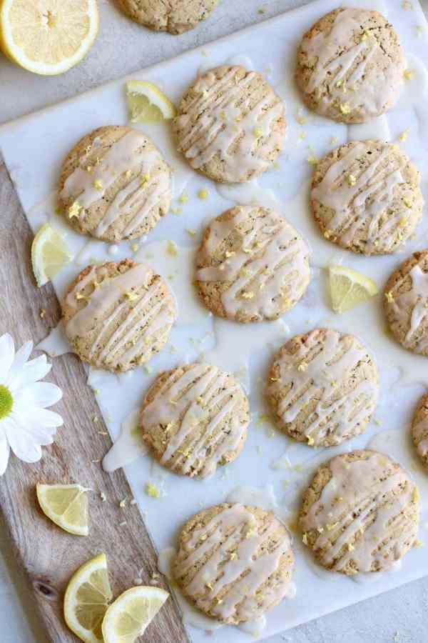 Overhead shot of the Paleo Lemon Poppy Seed Cookies single layered on a white marble cheese board and drizzled with a glaze and sprinkled with lemon zest.