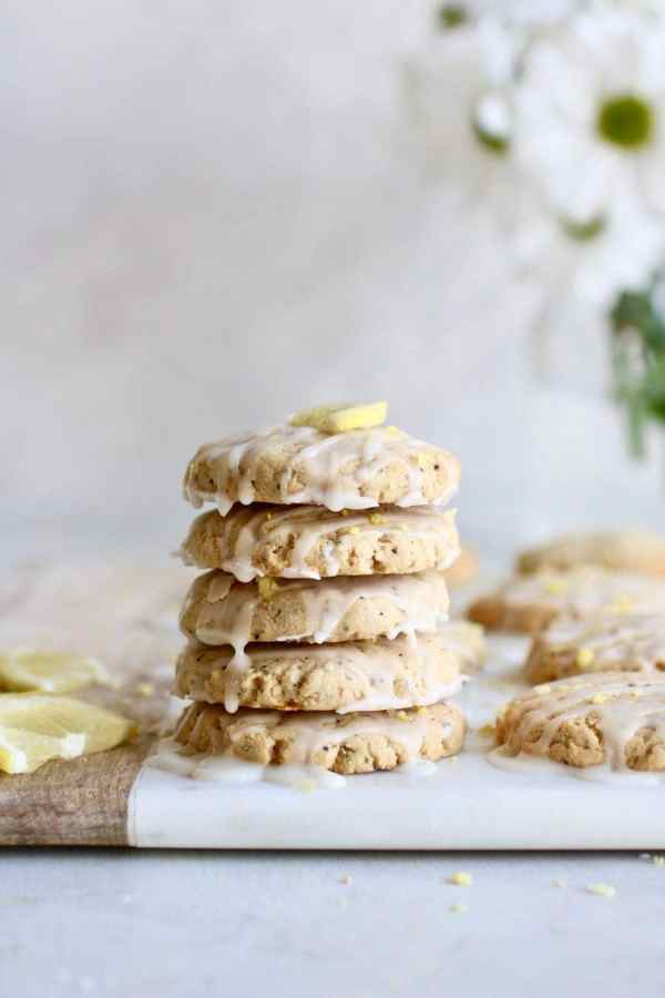 Photo of a stack of five Paleo Lemon Poppy Seed Cookies drizzled with a glaze.