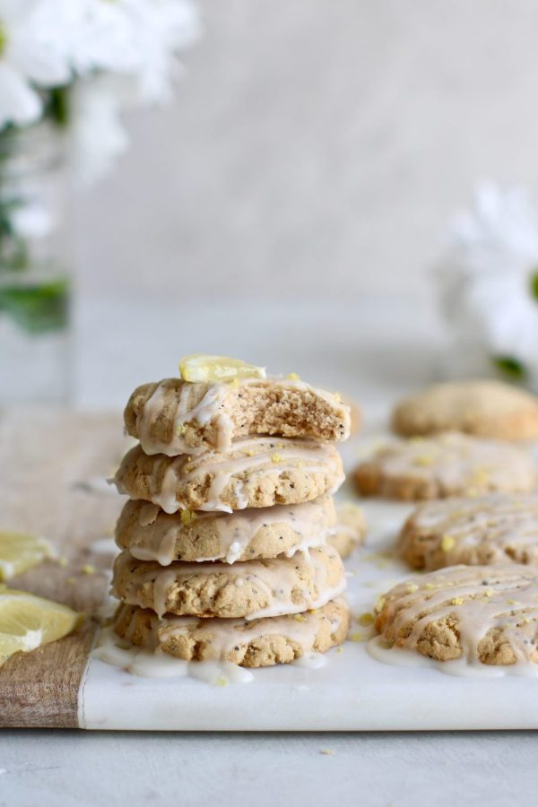 Photo of a stack of five Paleo Lemon Poppy Seed Cookies drizzled with a glaze. The top cookie has a perfect bite out of it.