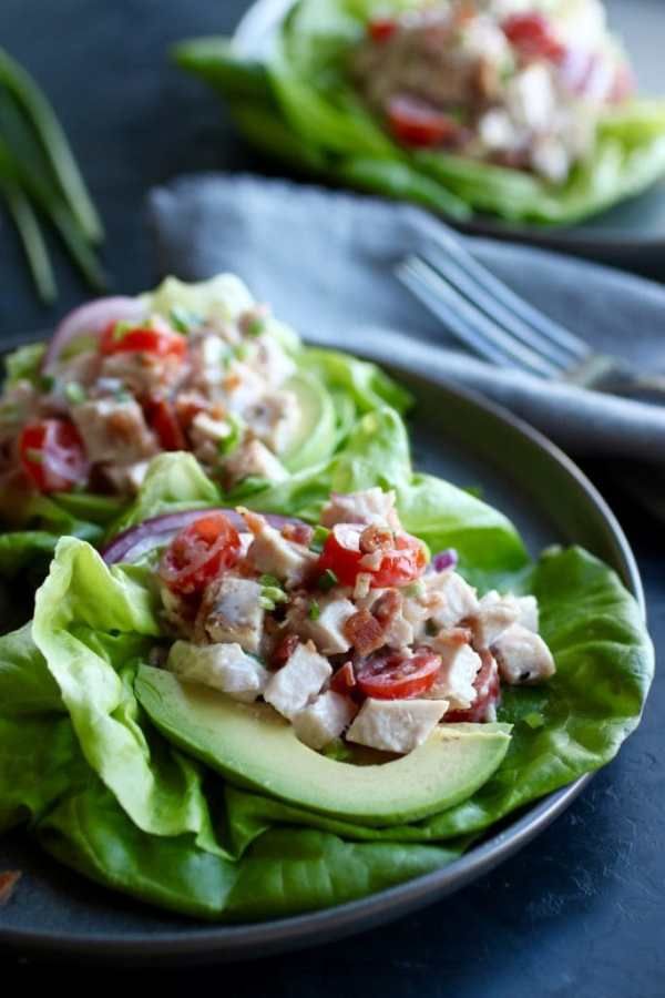 Plated chicken salad atop a lettuce leafs with tomato and avocado garnish with napkin and fork in the background