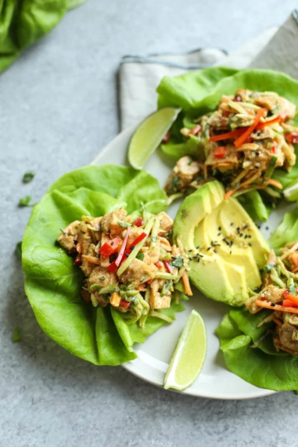 Asian chicken salad served on lettuce leaves on small plate with avocado and lime garnish