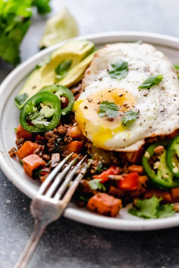 Tex-Mex Sweet Potato Hash served on a white plate with a fried-egg on top with the yolk running out of the egg.