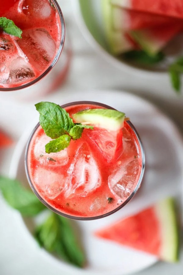 Photo of Watermelon Mojito on a white plate. Garnished with a mint leaf and small watermelon wedge.