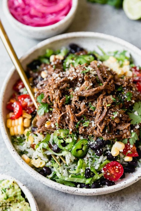 Instant Pot Beef Barbacoa served burrito bowl-style with a gold fork.