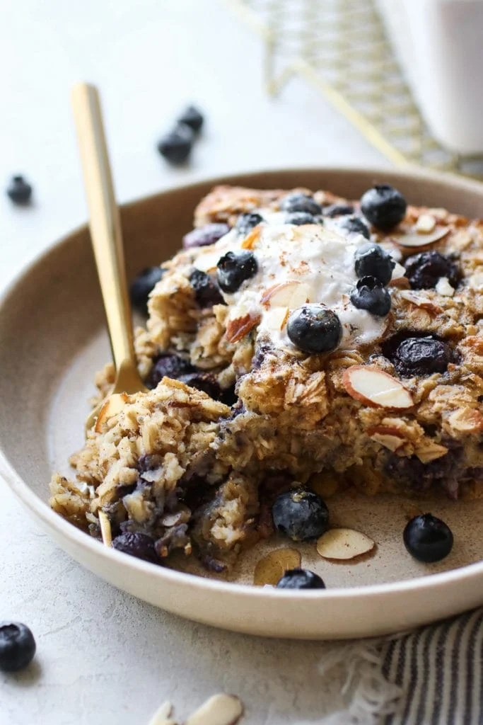 A serving Blueberry Baked Oatmeal on a small tan plate with a gold fork holding bite.