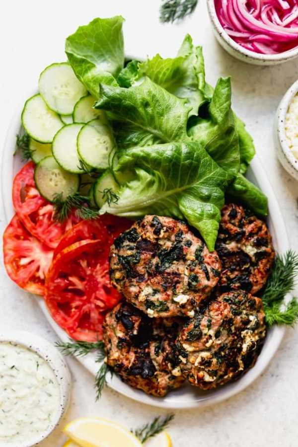 Large white platter holding the Grilled Turkey Burgers, tomato slices, lettuce leaf, cucumber slices and dill.