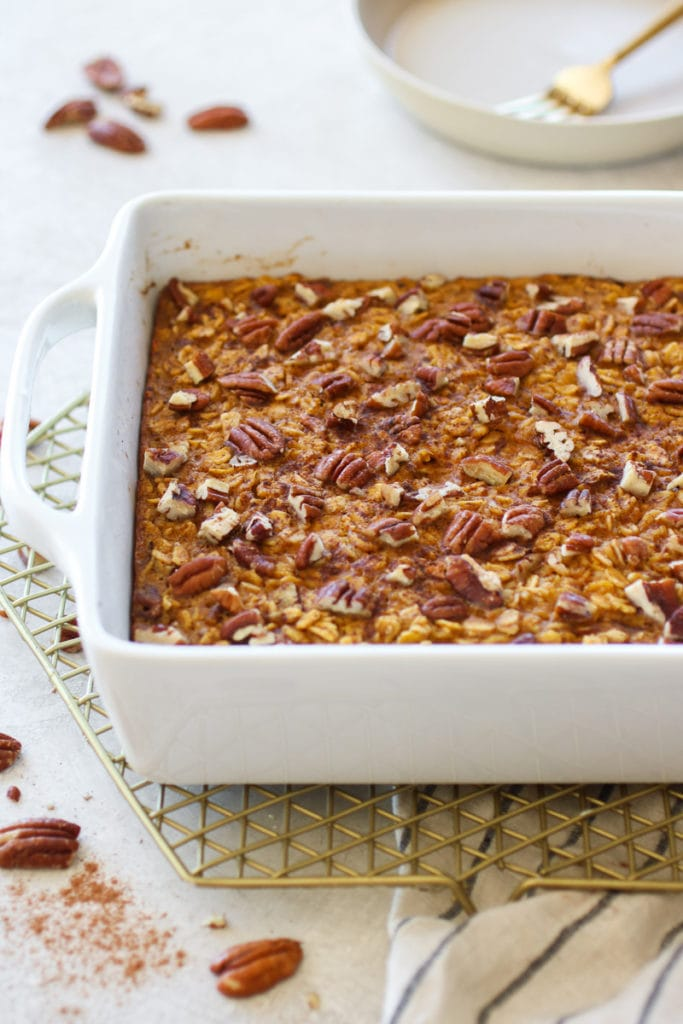 Pumpkin Baked Oatmeal fresh out of the oven in a white square dish sitting on a gold wire cooling rack.