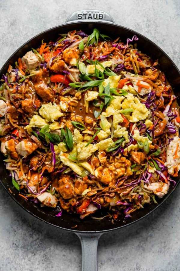 Healthy Chicken Pad Thai in a large cast iron skillet before tossing everything together.