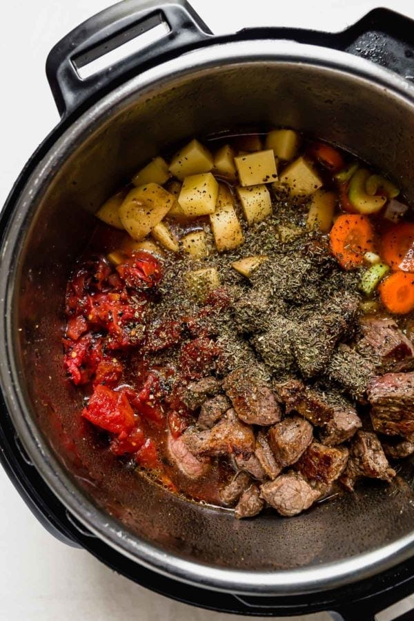 All ingredients for vegetable beef soup in an instant pot ready to be cooked.