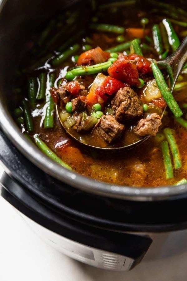Hearty beef and vegetable soup in an Instant Pot being ladled out