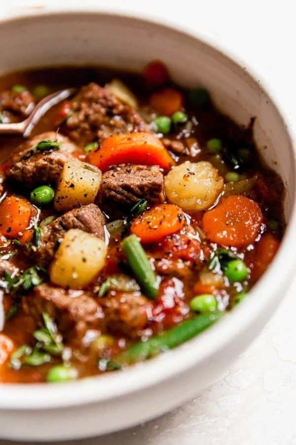 Chunky vegetable beef soup in a cream bowl with cracked pepper on top.