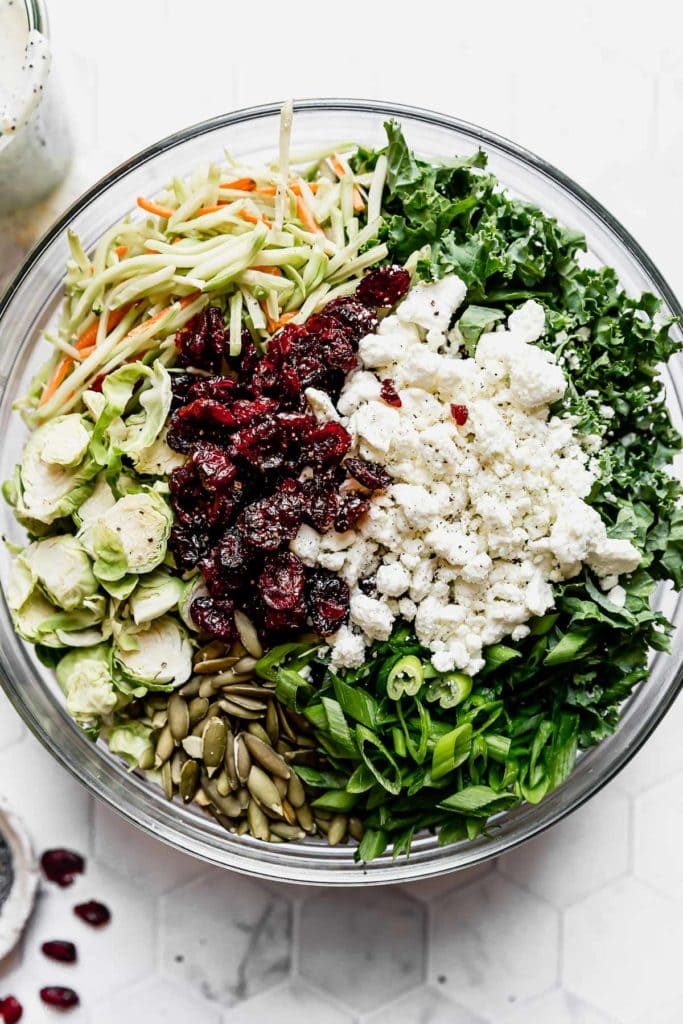 Sweet Kale Salad ingredients in a large clear bowl.