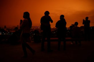 Visitors are seen in Dolores Park under an orange sky darkened by smoke from California wildfires in San Francisco, California, U.S. September 9, 2020. REUTERS/Stephen Lam/TPX IMAGES OF THE DAY