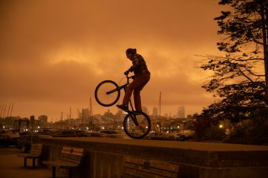 A man rides a bicycle on the beach as smoke from California wildlife hangs over the skyline on September 9, 2020 in San Francisco, California. Liu Guanguan/China News Service via Getty Images