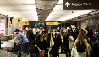 Travelers wearing protective face masks to prevent the spread of the coronavirus disease (COVID-19) reclaim their luggage at the airport in Denver, Colorado.