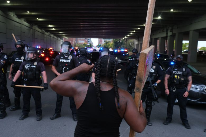 A demonstrator holding a cross gestures in front of a police line in Louisville