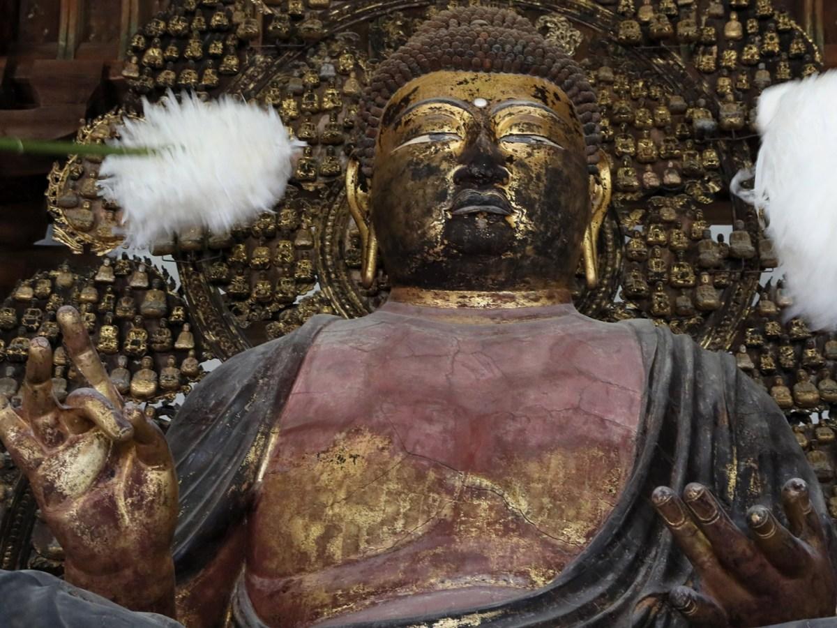 Monks dust a Buddhist statue