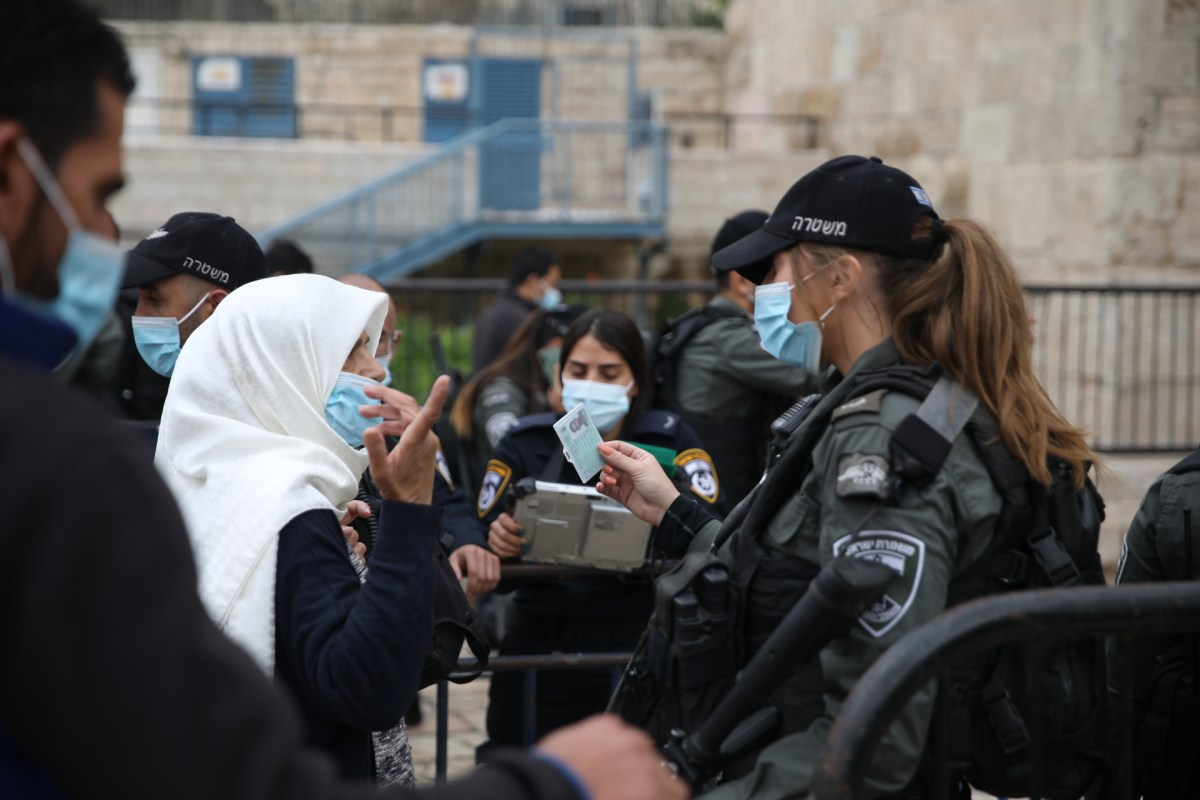 Israeli forces check a person's identification in front of the gates of Jerusalem's Old City
