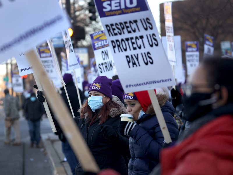 Healthcare workers with Cook County Health picket outside of Stroger Hospital as they stage a one-day strike on December 22, 2020 in Chicago, Illinois