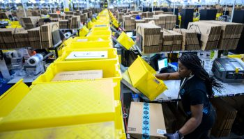 A woman works at a packing station at the 855,000-square-foot Amazon fulfillment center in Staten Island.
