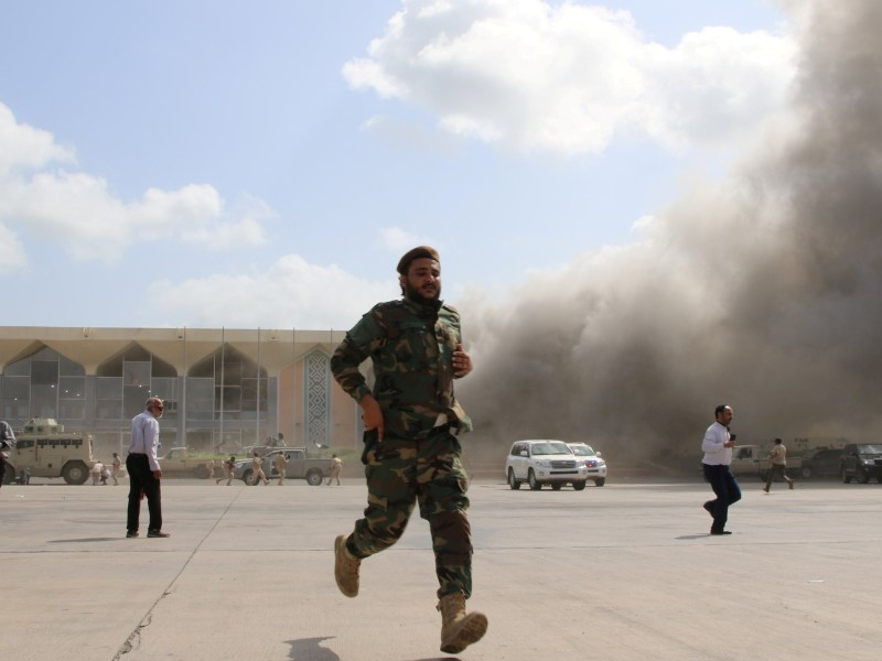 Security personnel and people react during an attack on Aden airport