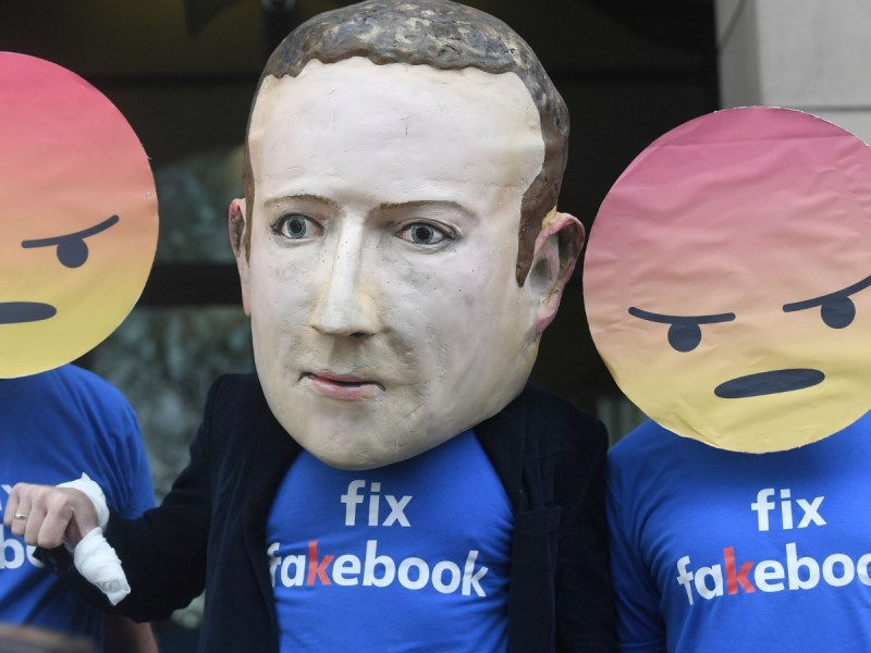 A Mark Zuckerberg figure with people in angry emoji masks