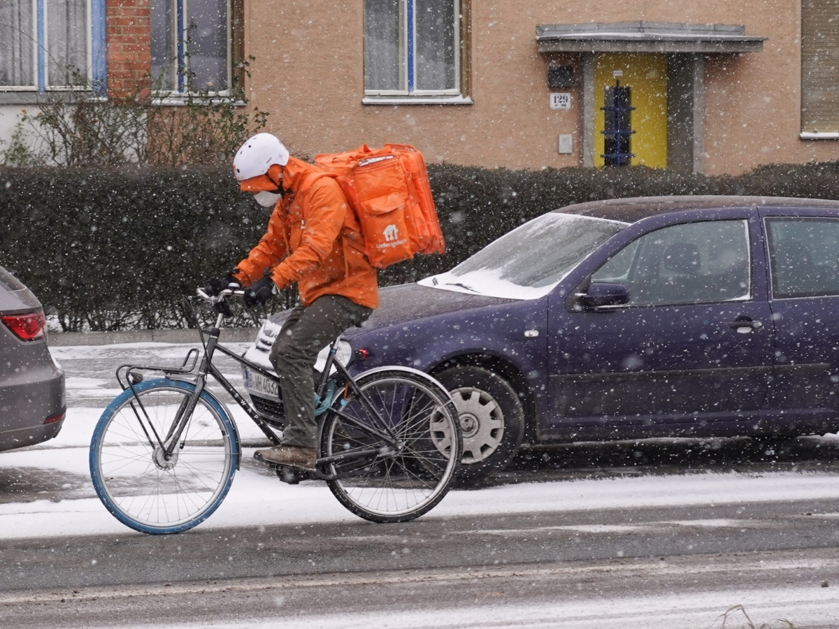 A delivery worker in Berlin on a bicycle, on a snowy street with cars