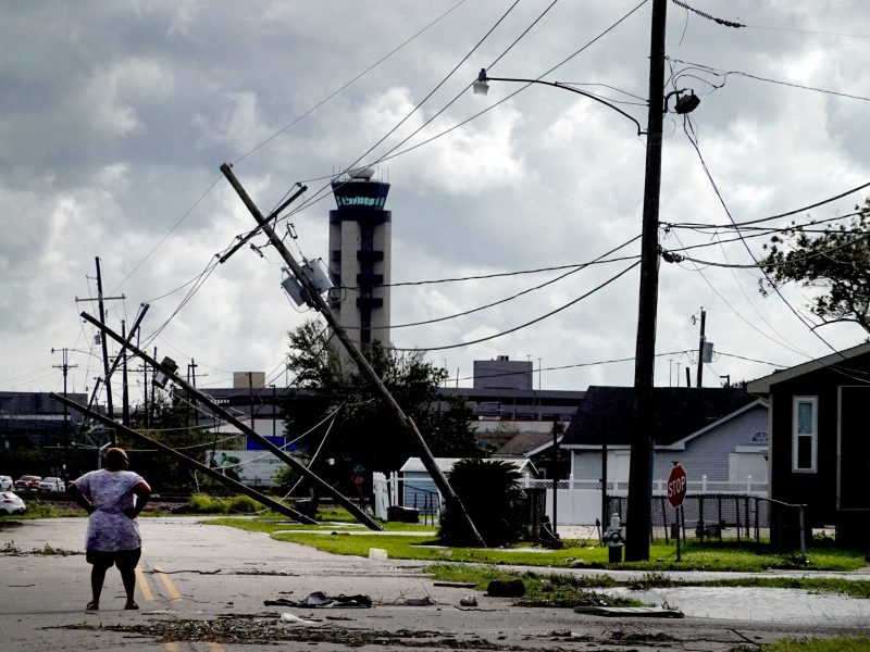 A woman stands in the street and surveys the damage to a neighborhood caused by Hurricane Ida