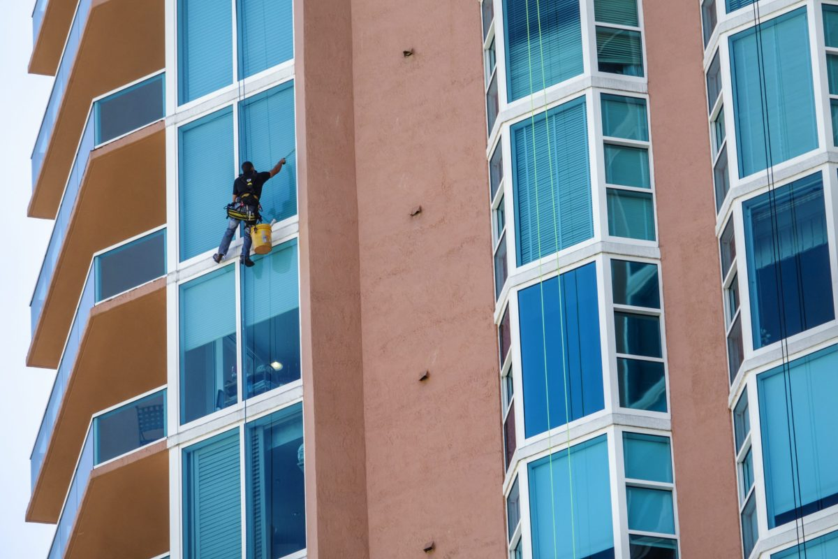 A high-rise window washer cleans windows