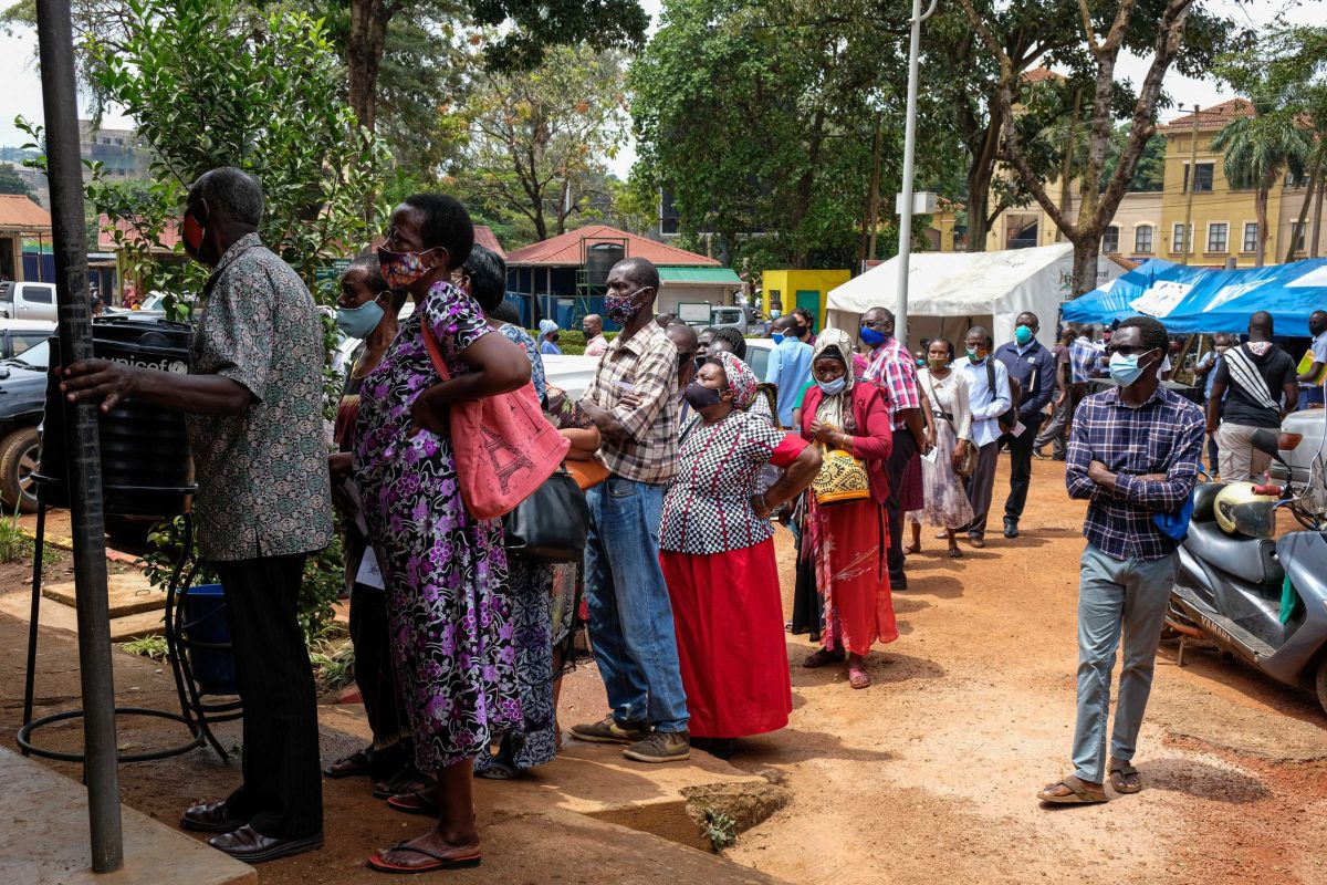 People wait in line to receive COVID-19 vaccine shots at Kiswa Health Centre III in Kampala, Uganda.