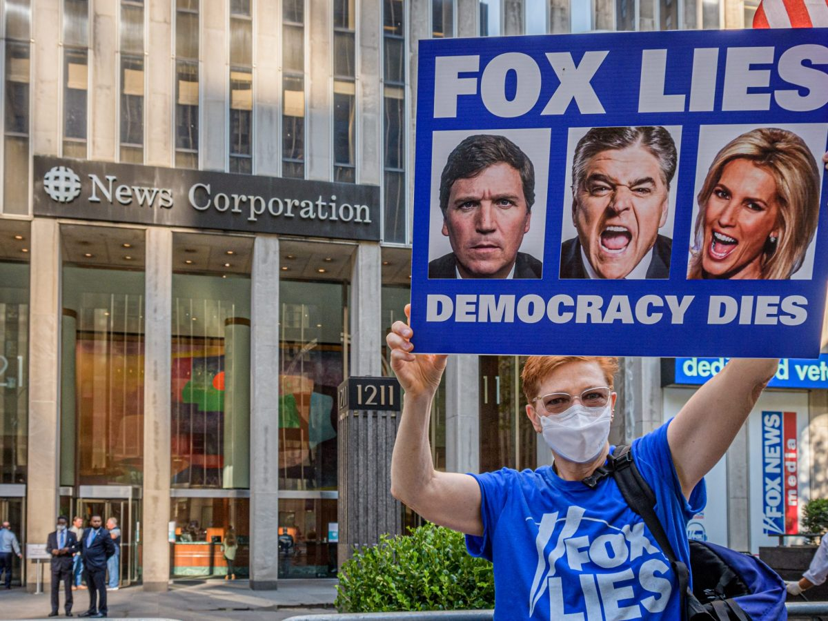 A protestor holding a sign stands outside the NewsCorp Building at 1211 6th Ave. in New York City