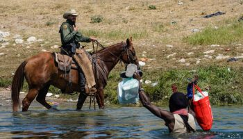 A United States Border Patrol agent on horseback tries to stop a Haitian migrant