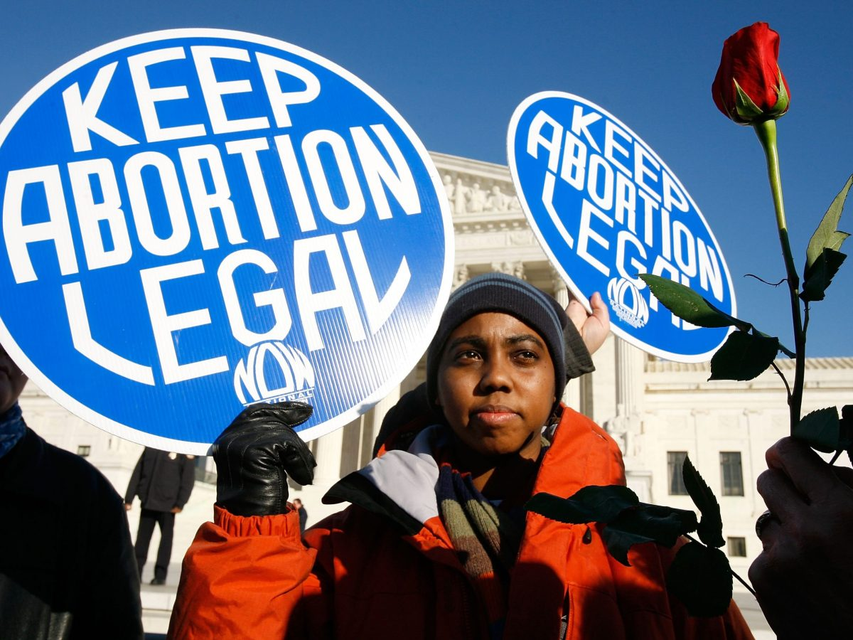 Pro-choice activist Lisa King holds a sign in front of the U.S. Supreme Court as a pro-life activist holds a rose nearby