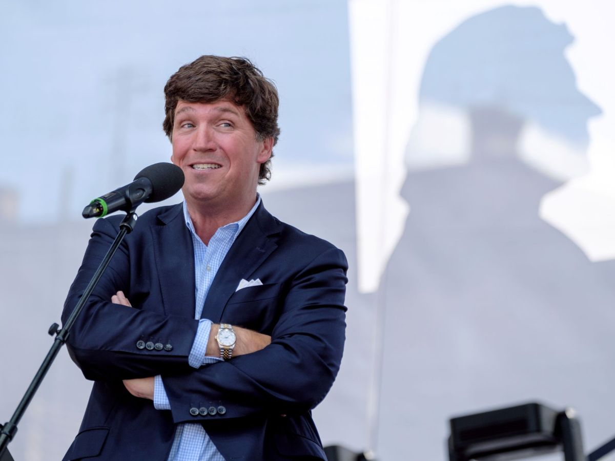 Tucker Carlson speaking into a microphone