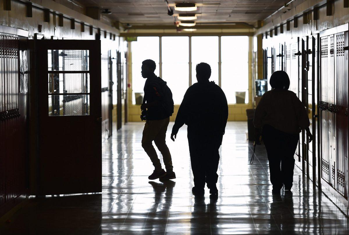 School police officer Tiffany Wiggins, right center, patrols a hallway at Edmondson-Westside High School