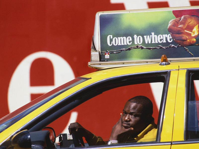 Stock photo of a tired New York City taxi driver sitting pensively in his cab