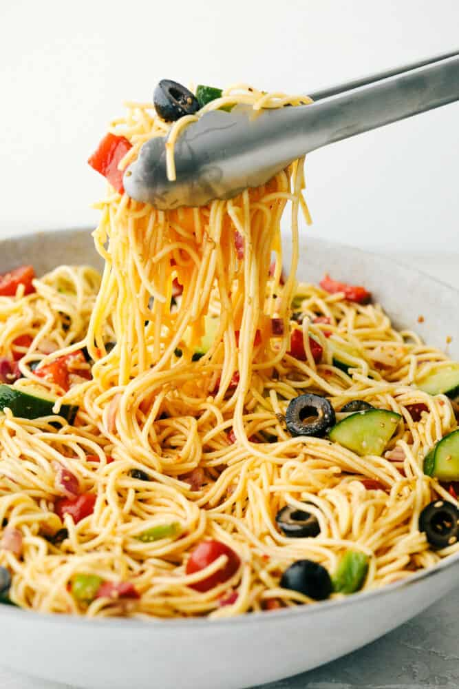 California spaghetti salad being lifted by the tongs.