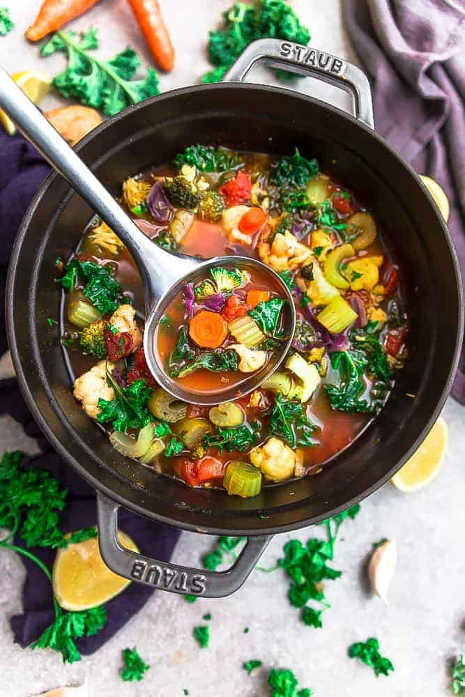 Vegetable detox soup in a pot with ladle